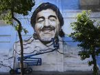 TOPSHOT - Argentine street artist Alfredo Segatori controls an elevator he uses to paint a mural of late Argentine football legend Diego Maradona in Buenos Aires, on December 1, 2020. (Photo by JUAN MABROMATA / AFP)