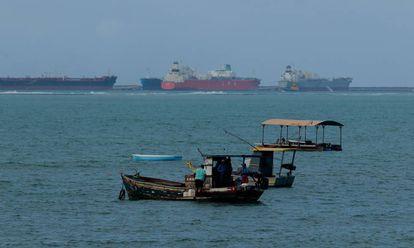 Pescadores na praia de Gaibu (PE), com os navios no porto de Suape ao fundo.