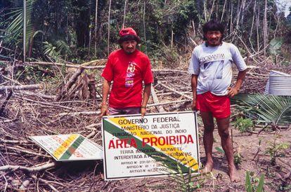 Homens da tribo Araweté junto à placa de demarcação da Terra Indígena Araweté, no Pará