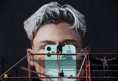Trabalhadores constroem mural de anúncio de smartphone em Berlim, em outubro de 2020.