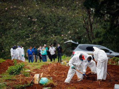 Trabalhadores enterram uma vítima de covid-19 nesta quinta-feira no Cemitério Viola Formosa, em São Paulo (Brasil).