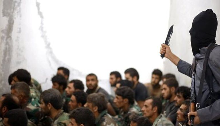 Um membro do Estado Islâmico segura uma faca junto a um grupo de soldados sírios capturados em Raqa.