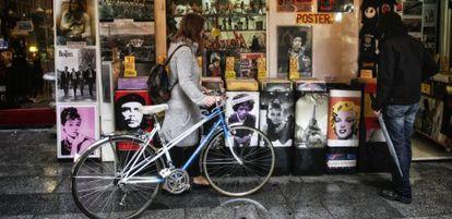 Jovem olha discos de vinil junto a sua velha bicicleta.