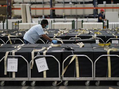 Um trabalhador da contagem de votos move máquinas de votação no Clark County Election Department, em Las Vegas, Nevada.