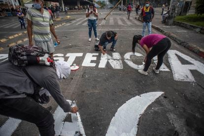 Jovens colombianos fazem pichações de protesto em uma avenida da cidade de Cali, Colômbia, em 8 de maio
