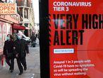 -FOTODELDÍA- LONDRES, 19/12/2020.- Viandantes pasan junto a un anuncio del Gobierno británico sobre el coronavirus. Londres, el sureste y este de Inglaterra pasarán este domingo al nivel 4, grave, de riesgo de covid-19, con el cierre de tiendas no esenciales, por el alza de los casos del virus, anunció este sábado el primer ministro británico, Boris Johnson. EFE/NEIL HALL