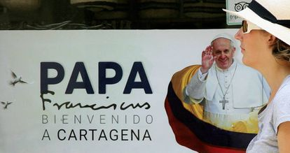 Mulher diante de cartaz do papa Francisco