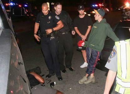 Justin Bieber fala com a polícia enquanto espera a ambulância.