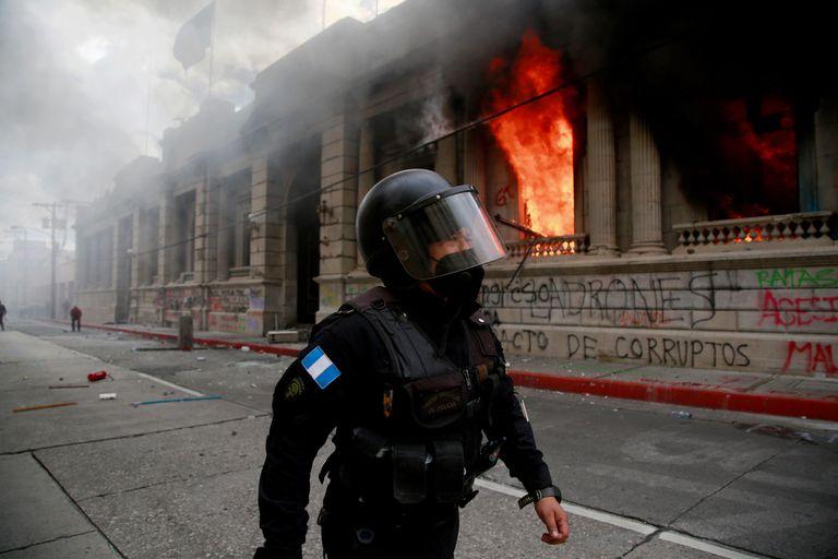 Policial caminha ao lado do Congresso em chamas na Cidade da Guatemala, neste sábado.