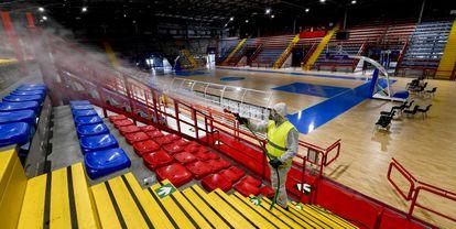 Um agente dos Serviços de saúde de Nápoles higieniza as instalações esportivas do ginásio Palabaruto.