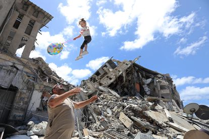 Um palestino brinca no sábado com uma garota ao lado dos escombros de uma casa bombardeada, em Gaza.
