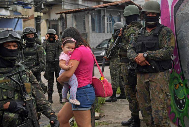 Mulher carrega bebê na comunidade Vila Kennedy, no Rio.