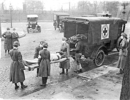 Enfermeiras da Cruz Vermelha transportam vítima da gripe de 1918 em Sant Louis (Missouri).