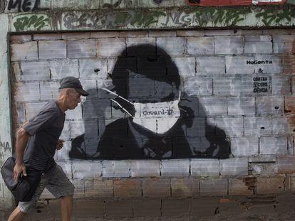 Um homem passa por um grafitti de Jair Bolsonaro durante a pandemia de coronavírus, no Rio de Janeiro, nesta terça-feira.