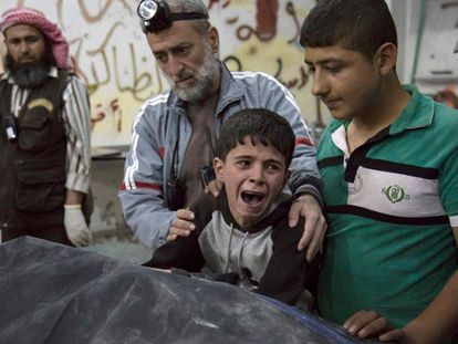 Criança junto ao cadáver de um parente depois do bombardeio em Aleppo.