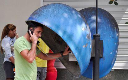 Cubano usa telefone público em Havana.