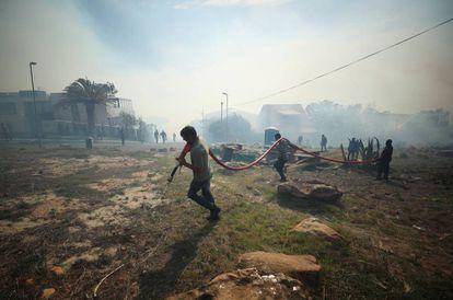 Moradores e bombeiros voluntários lutam para conter um incêndio, atiçado por fortes ventos, nas encostas da Table Mountain, na Cidade do Cabo.