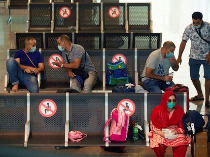 Viajantes com máscaras protetoras aguardam seu voo no aeroporto de Barcelona.