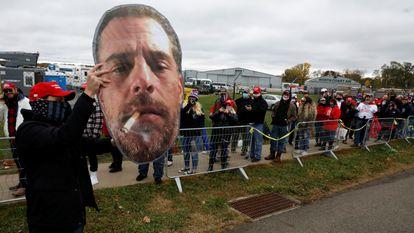 Um seguidor de Trump mostra uma foto de Hunter Biden na fila de um comício do presidente em Erie (Ohio).