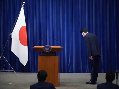 O primeiro-ministro do Japão, Shinzo Abe, se curva diante da bandeira japonesa ao anunciar a decisão de deixar o cargo que ocupa há oito anos, por motivos de saúde.