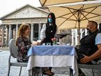 A waiter serves coffee to customers at a cafe terrace by the Pantheon monument in central Rome on May 18, 2020 during the country's lockdown aimed at curbing the spread of the COVID-19 infection, caused by the novel coronavirus. - Restaurants and churches reopen in Italy on May 18, 2020 as part of a fresh wave of lockdown easing in Europe and the country's latest step in a cautious, gradual return to normality, allowing businesses and churches to reopen after a two-month lockdown. (Photo by ANDREAS SOLARO / AFP)