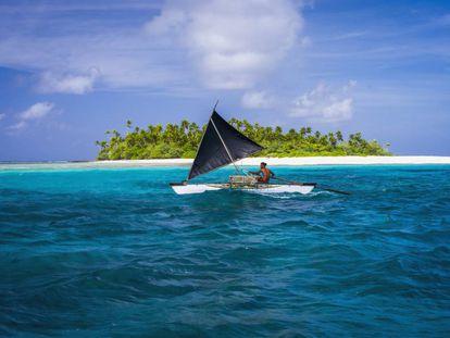Embarcação tradicional em frente a um dos atóis da república insular de Kiribati, no oceano Pacífico.
