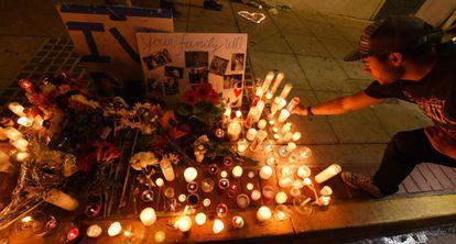 Um estudante deixa uma vela pelas vítimas do massacre.