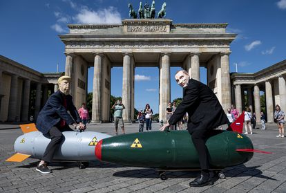 Manifestantes com máscaras de Trump e Putin posam sobre duas bombas falsas durante protesto contra armas atômicas em Berlim, na Alemanha.