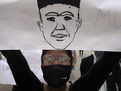 Manifestante carrega cartaz com o rosto de João Pedro desenhado, em protesto em São Gonçalo em 5 de junho.