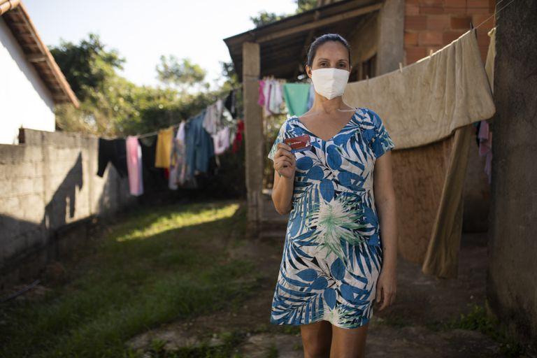 Luciana de Souza Nunes mostra o cartão com o auxílio da prefeitura em sua casa, em Maricá.