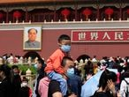 FIEL - In this May 3, 2021, file photo, a man and child wearing masks visit Tiananmen Gate near the portrait of Mao Zedong in Beijing. China's ruling Communist Party is looking at allowing easing birth limits further to allow couples to have three children instead of two in response to the population's rising age, a state news agency said Monday, May 31, 2021. (AP Photo/Ng Han Guan, File)