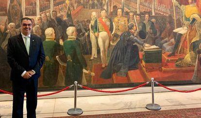 Lafayette Andrada posa no Itamaraty, em frente à obra que mostra a coroação de Dom Pedro I