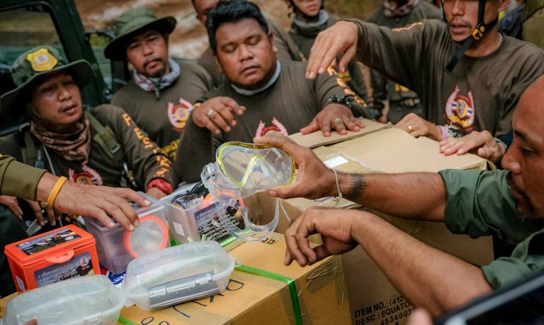 Responsáveis pelo resgate preparam óculos de mergulho para enviá-los aos meninos da gruta.