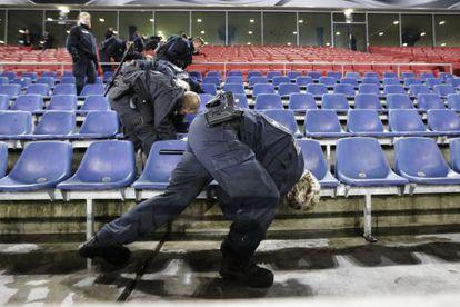 Policiais inspecionam as grades do estádio de Hanover.