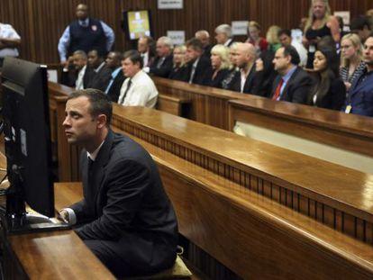 Oscar Pistorius sentado no banco dos réus minutos antes do começo do seu julgamento na Pretória.