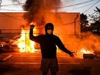 (FILES) In this file photo a protestor gestures as cars burn behind him during a demonstration in Minneapolis, Minnesota, on May 29, 2020 over the death of George Floyd, a black man who died after a white policeman kneeled on his neck for several minutes. - The body of an unidentified man was found early May 31, 2020 near a burning vehicle in Minneapolis, police in the protest-rocked northern US city said. Police spokesman John Elder said the body showed obvious signs of trauma, and the death was under investigation by the city's homicide unit.It was unclear if it was related to protests that have swept the city since the death on Monday of George Floyd, an unarmed black man whose death in police custody has ignited nationwide unrest. (Photo by CHANDAN KHANNA / AFP)