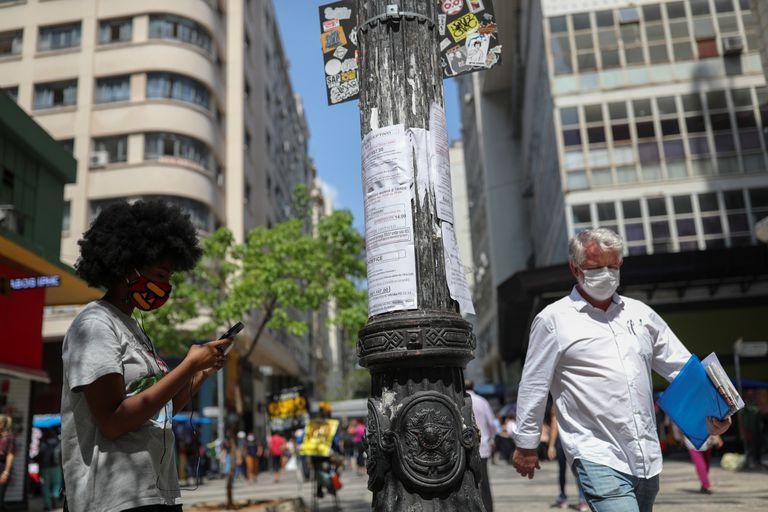 Mulher anota em seu telefone uma oportunidade de emprego a partir de listas postadas em um poste de luz no centro de São Paulo no final de setembro.