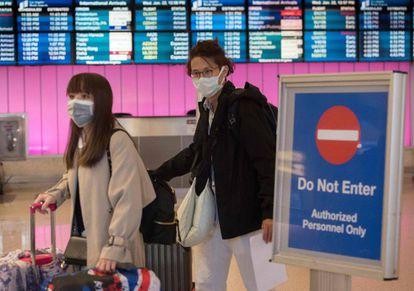 Passageiros com máscaras ao desembarcarem no aeroporto de Los Angeles, na quarta-feira.