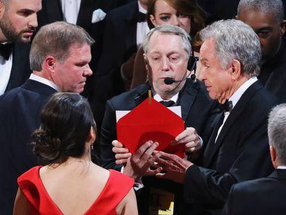 Brian Cullinan (à esquerda e com expressão séria), da PriceWaterHouseCoopers, fala com Warren Beatty no palco. De costas, de vestido vermelho, a outra auditora da PWC, Martha Ruiz.