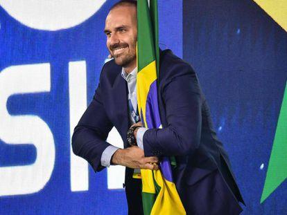 Eduardo Bolsonaro abraça bandeira do Brasil durante evento conservador em São Paulo, no dia 11 de outubro.