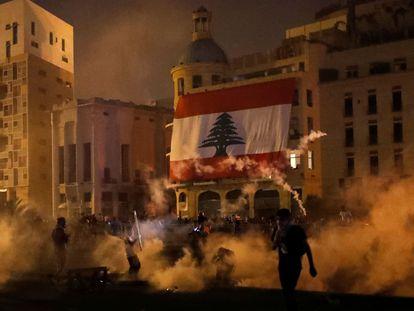 Manifestantes entre gases lacrimogêneos lançados pelas forças de segurança protestam nas proximidades do Parlamento, em Beirute, no sábado.