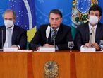 Brazilian President Jair Bolsonaro (C) talks next to Brazilian Minister of Economy, Paulo Guedes (L) and Brazilian Minister of Health Henrique Mandetta (R) during a press conference regarding the COVID-19, coronavirus pandemic at the Planalto Palace, Brasilia on March 18, 2020. (Photo by Sergio LIMA / AFP)