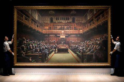Dois funcionários da Sotheby's mostram o quadro 'Devolved Parliament' aos participantes do leilão.