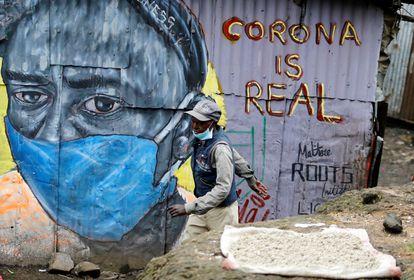 Um homem passa em frente a um mural que adverte sobre o coronavírus no bairro de Mathare, em Nairóbi, capital do Quênia.