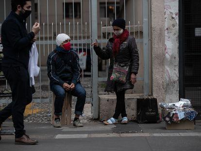Pessoas protegidas com máscaras transitam em uma rua de São Paulo.