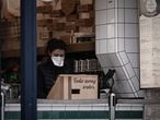 A woman wearing a protective mask stands at a counter of a restaurant selling take away food in Paris on March 16, 2020, as all non-essential public places including restaurants and cafes have been closed to prevent the spread of the Covid-19, caused by the novel coronavirus. - France will progressively reduce long-distance train, bus and plane travel over the coming days in a bid to limit the spread of the coronavirus, the government announced on March 15. The country has already shuttered cafes, restaurants, schools and universities and urged people to limit their movements. (Photo by Philippe LOPEZ / AFP)