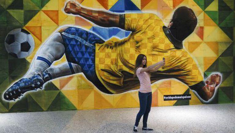 Uma garota tira uma foto em frente a painel no aeroporto de Brasília.