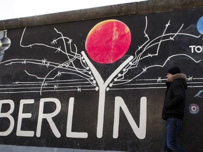 BERLIN, GERMANY - FEBRUARY 05: Vsitor passing a painting at the Berlin Wall at the East Side Gallery on February 5, 2018 in Berlin, Germany. Today tem been 10,316 days since the Berlin Wall officially fell, the same number of days that it stood between 1961 and 1989. The Berlin Wall, built by the communist authorities of East Germany, divided capitalist West Berlin from communist East Berlin and came to symbolize the Cold War between the western Allies, led by the United States, and the Eastern Bloc, led by the Soviet Union. (Photo by Carsten Koall/Getty Images)