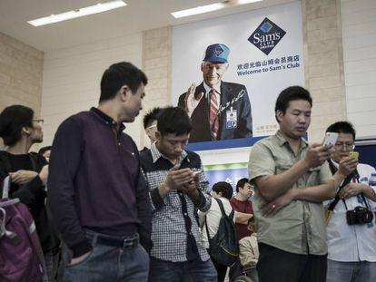 Vários clientes revisam seus celulares em um supermercado de Tianjin (China), em 28 de setembro.