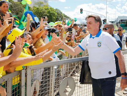 Bolsonaro, que deveria estar em isolamento por ter tido contato com infectados com coronavírus, cumprimenta e toca apoiadores em Brasília.
